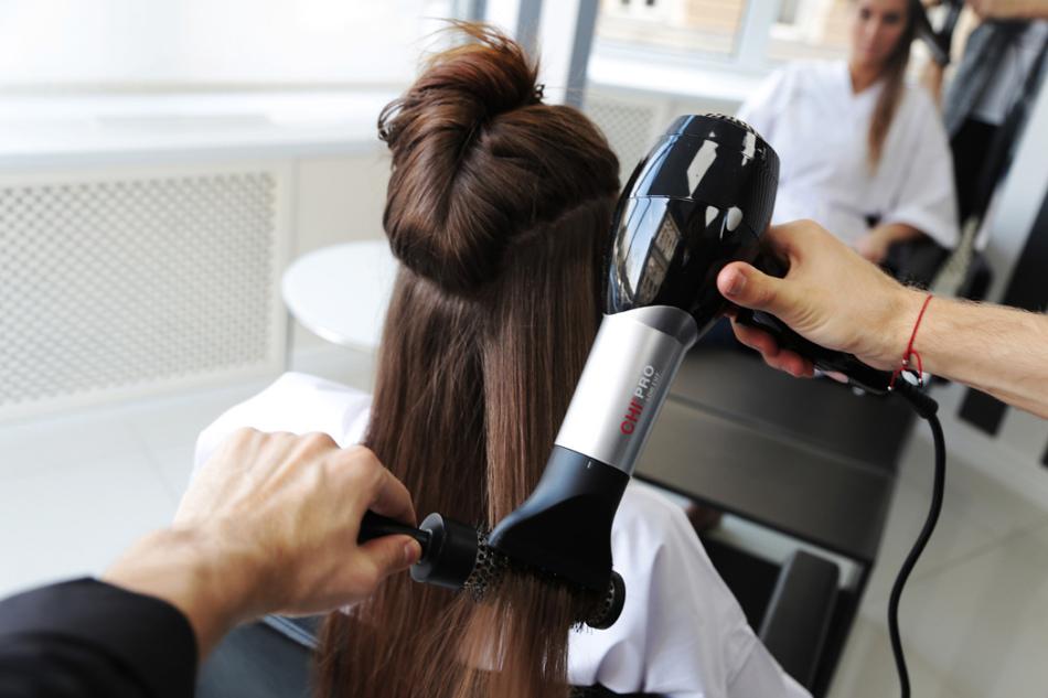 Парикмахер сушит клиентке волосы феном