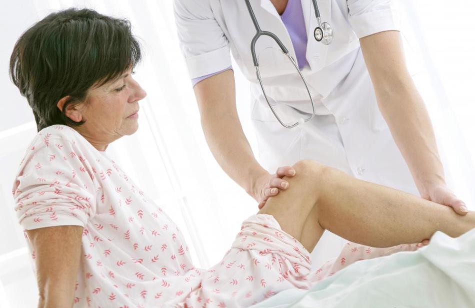 Доктор осматривает больное колено