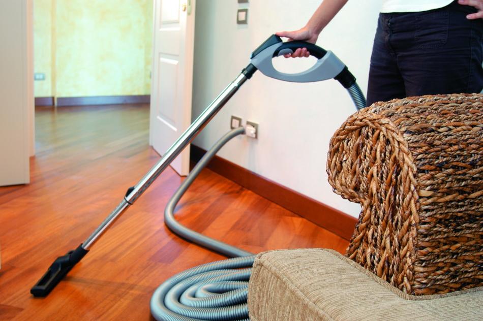 Девушка убирает в комнате с помощью пылесоса