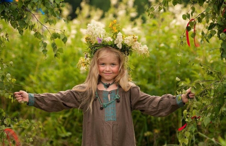 Улыбчивая девочка в венке из полевых цветов во время празднования дня летнего солнцестояния