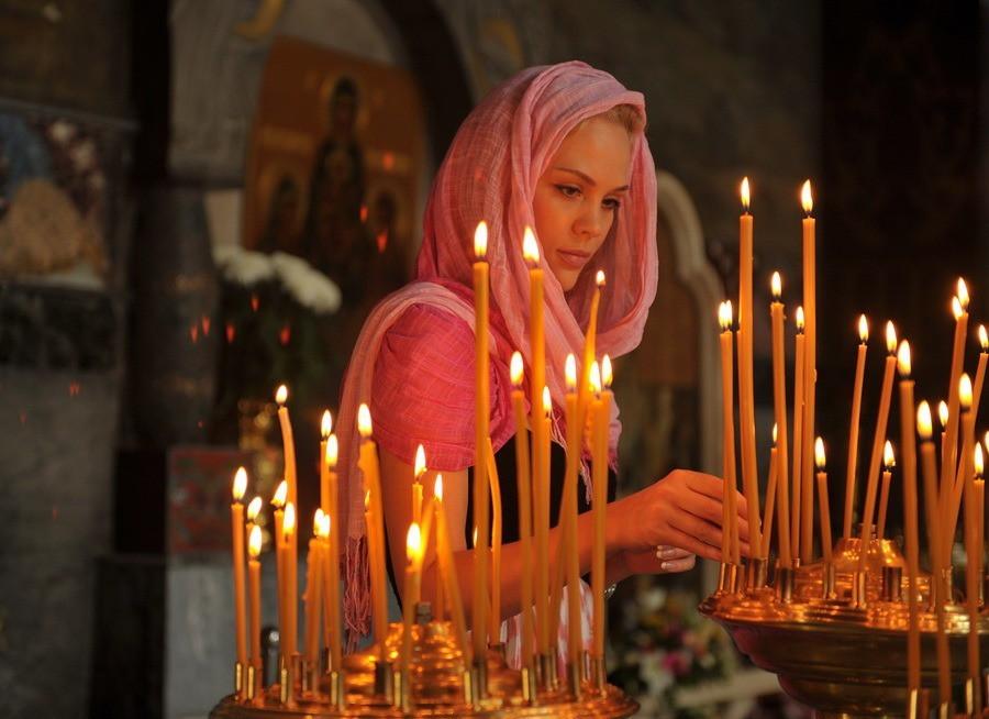 Девушка молится в церкви и ставит свечи