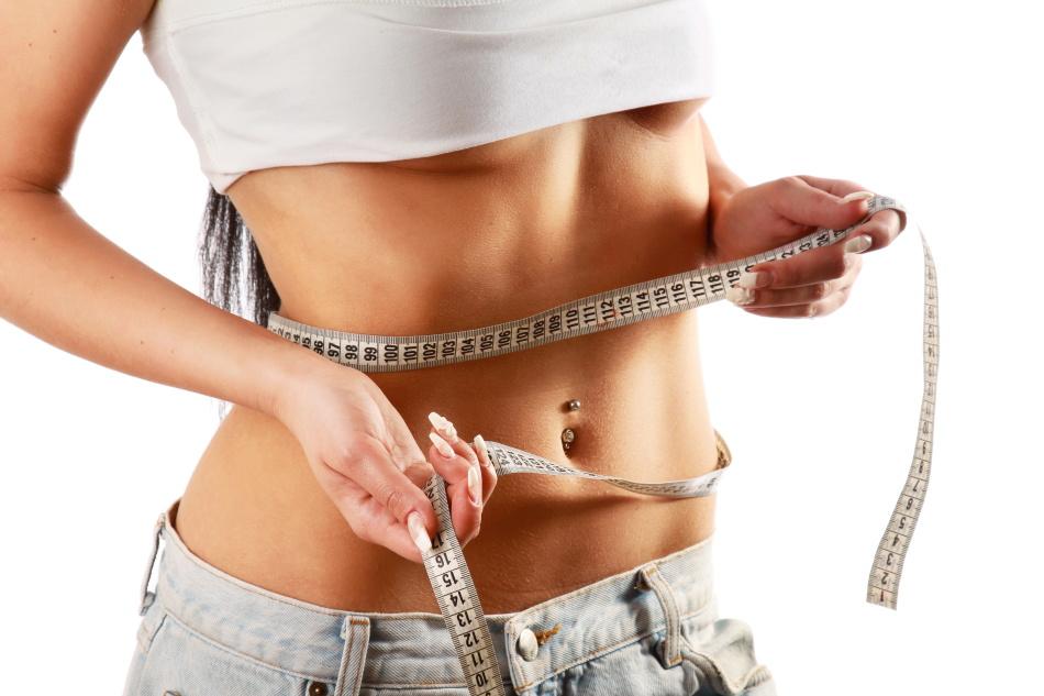 Девушка измеряет обхват своей талии после клубничной диеты