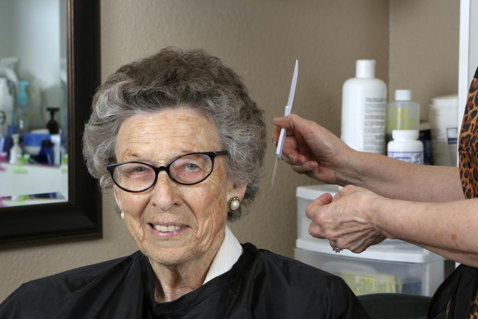 Пожилая женщина в кресле в салоне перед покраской своих седых волос