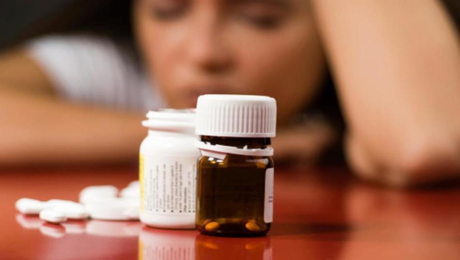 Грустная девушка сидит за столом перед открытыми банками с антидепрессантами при похудении