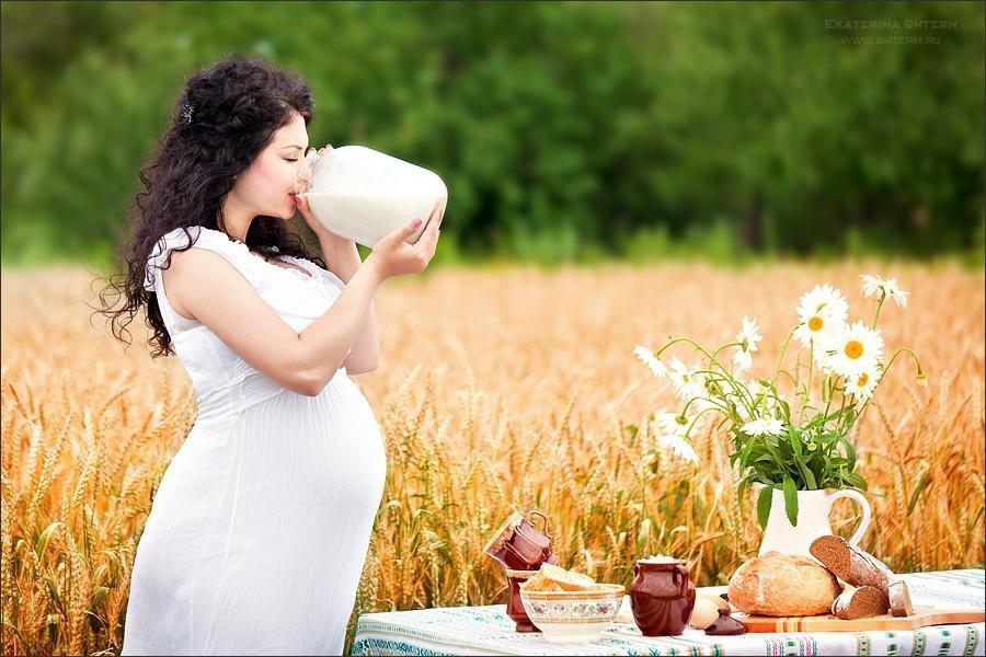Красивая беременная женщина на пшеничном поле кушает