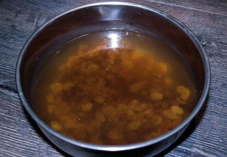 Изюм в ёмкости с водой замачивается перед приготовлением кутьи