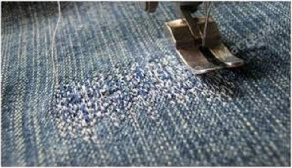 Джинсы под лапкой швейной машинки перед пришиванием заплатки