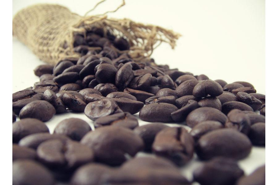 Зерна натурального кофе рассыпаны на столе перед измельчением для покраски седых волос