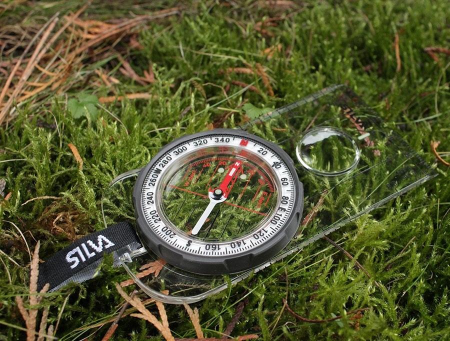 Компас лежит на траве перед определением сторон света и ориентации на местности