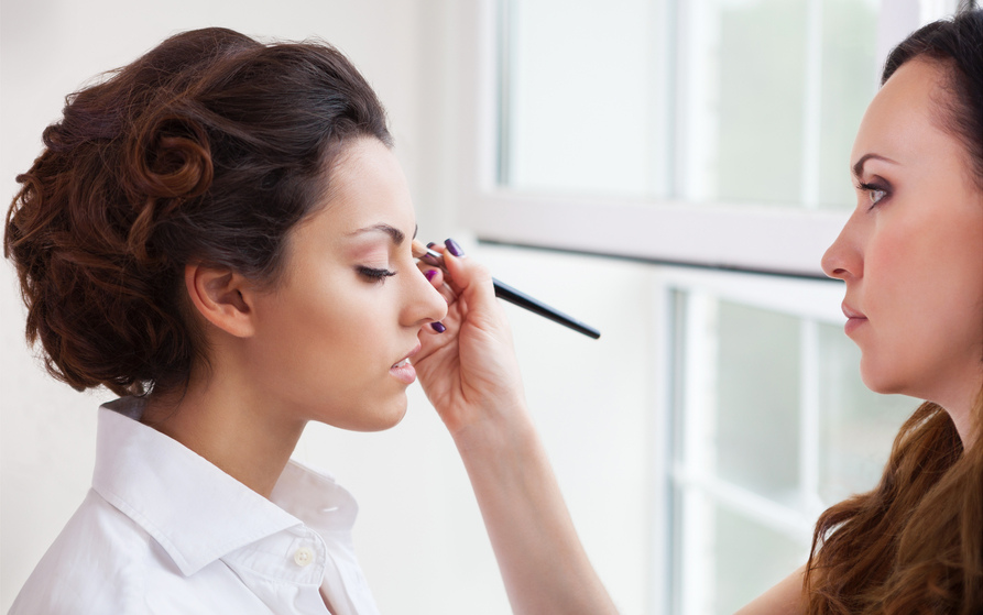 Визажист выполняет макияж невесте