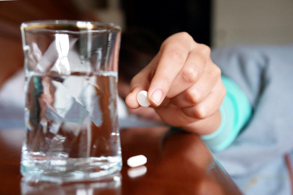 Девушка держит в руке таблетку антижепрессанта для приема от плаксивости