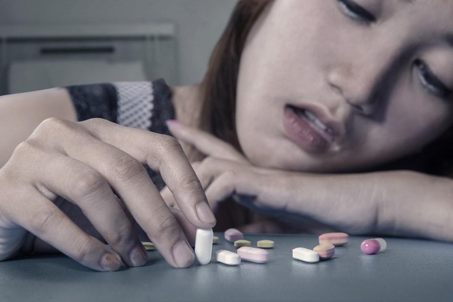 Девочка-подросток сидит за столом с горстью антидепрессантов