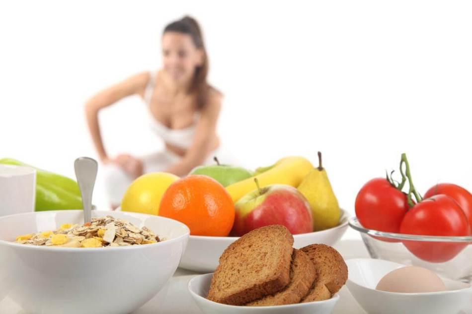 На столе блюда, полезные к приему в дни тренировок, и улыбчивая девушка за ними выполняет упражнения