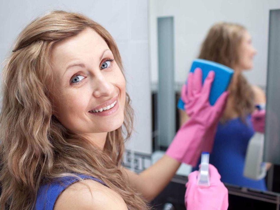 Улыбчивая девушка натирает зеркало до блеска