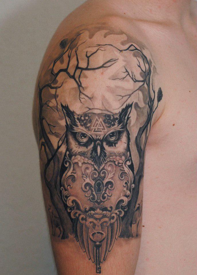 Татуировка в виде совы на мужском плече