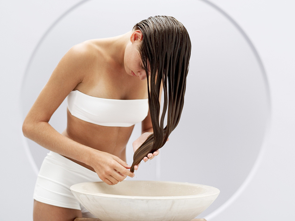 Девушка смываем маску с волос
