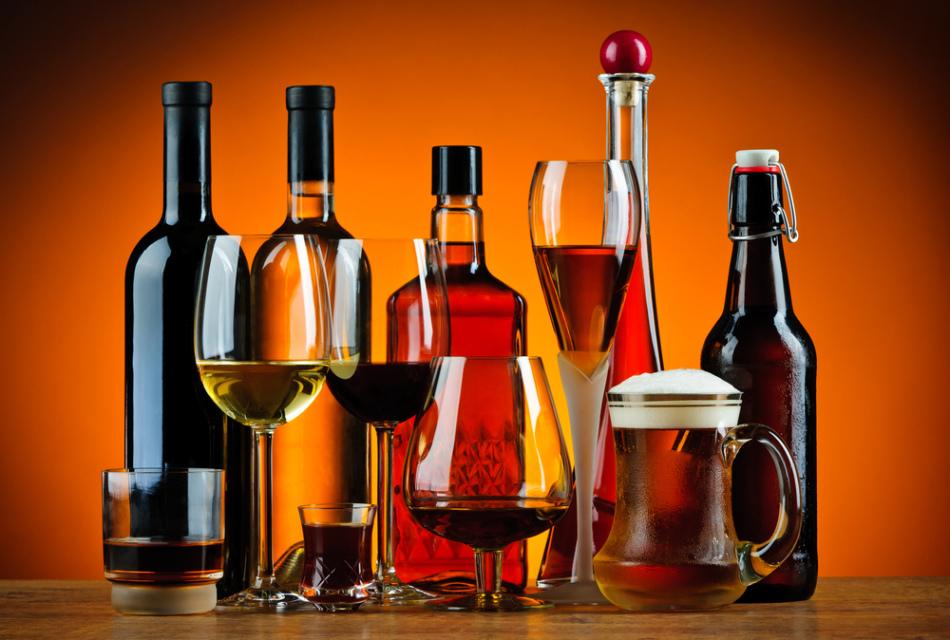 Бутылки и бокалы с разными видами алкогольных напитков