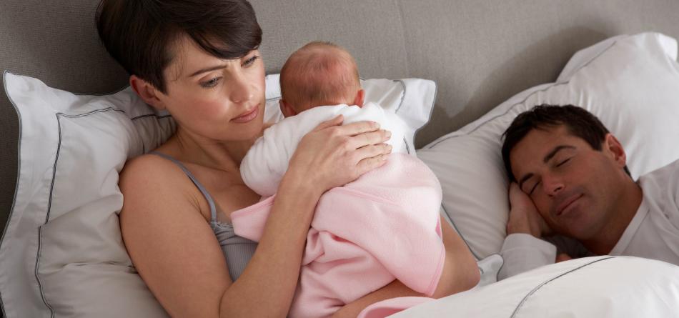 Уставшая молодая мама держит малыша на руках