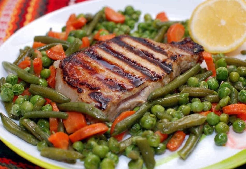 Жаренная свинная отбивная на тарелке с гарниром из размороженных овощей