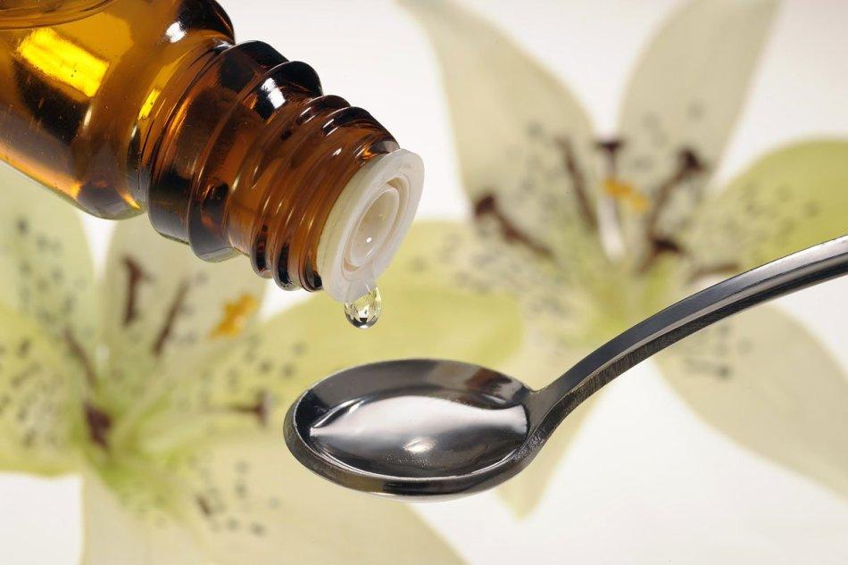 Жидкое лекарство капают в чайную ложку для определения количества капель в ней