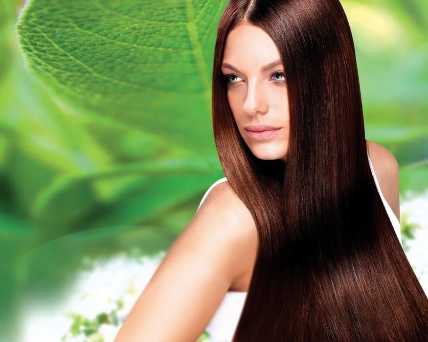 Длинные волосы девушки на фоне листа лопуха