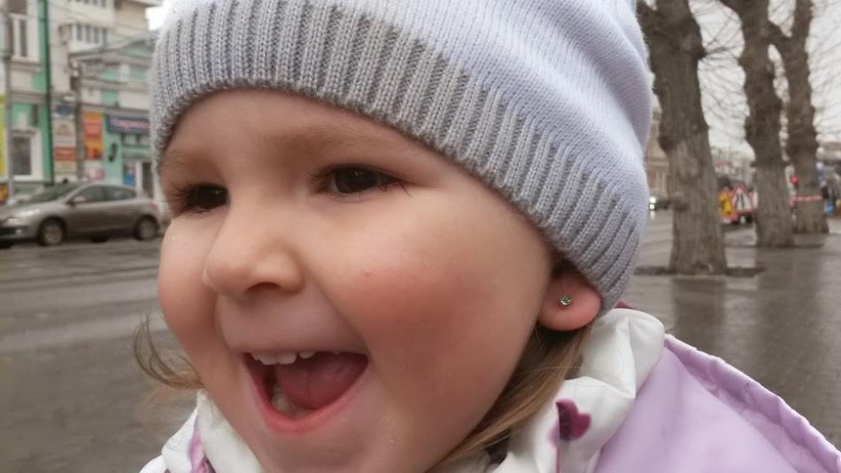 Девочка с проколотыми ушами в шапке
