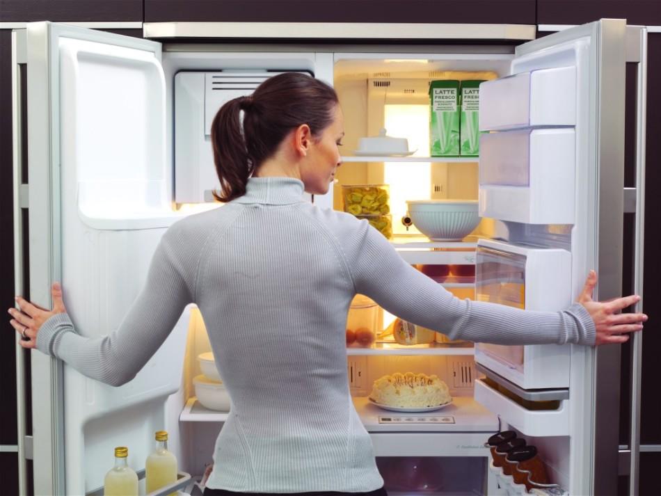 Девушка проверяет контейнеры с сухофруктами в холодильние, которые стоят на хранении