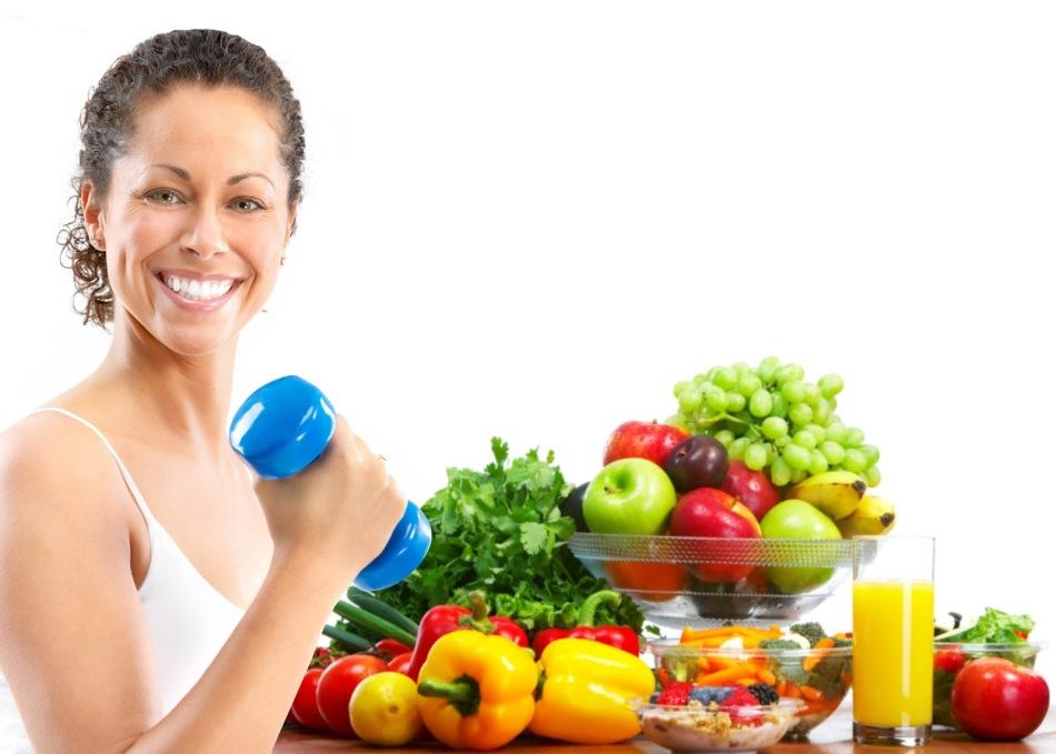 Улыбчивая брюнетка с гантелей в руке на фоне овощей и фруктов, которые можно кушать после тренировки