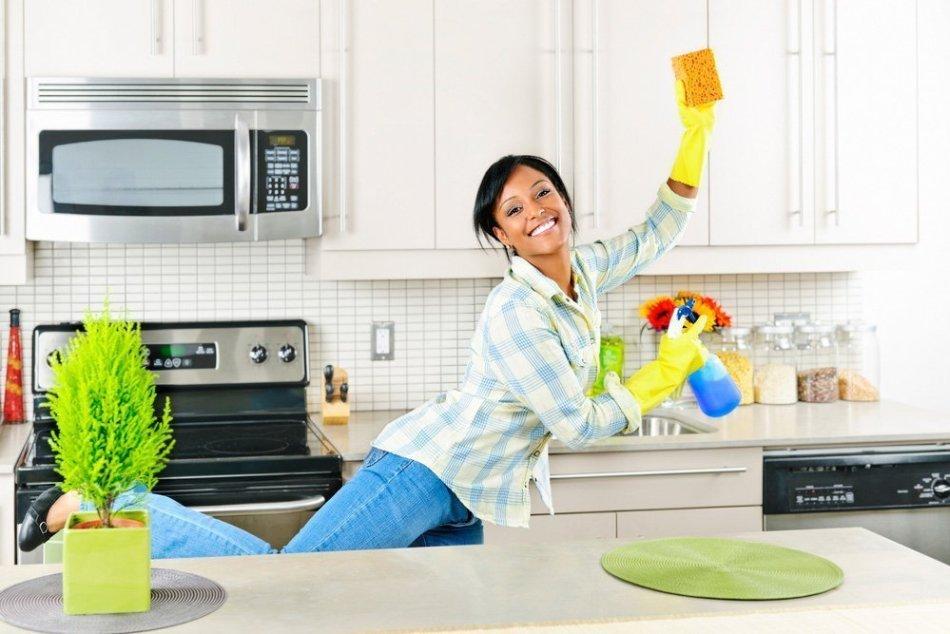 Улыбчивая девушка убирает на кухне по системе флай леди