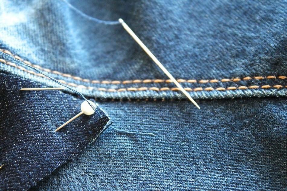Зафиксированная шпильками заплатка на джинсах перед пришиванием вручную