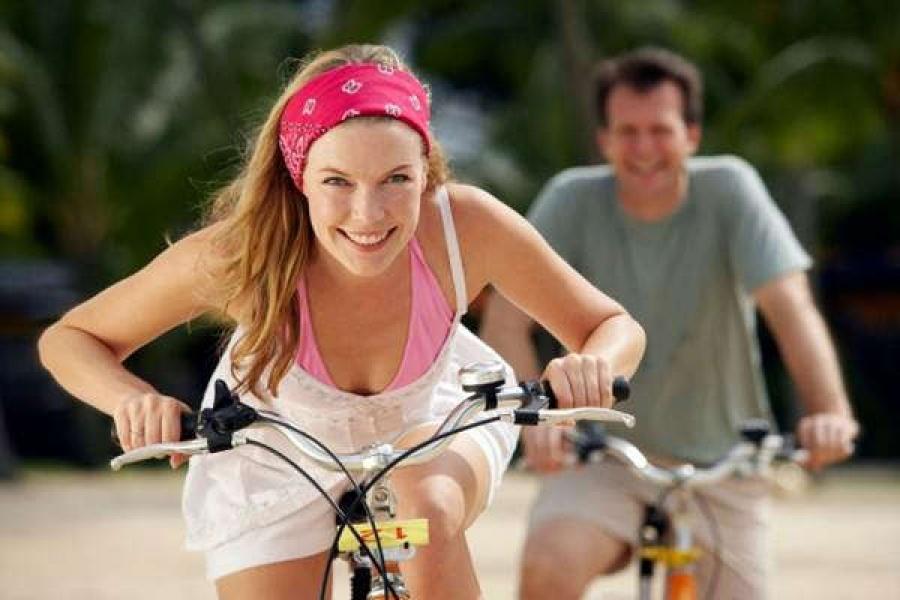 Улыбчивая блондинка едет на велосипеде и не чувствует боли в коленях
