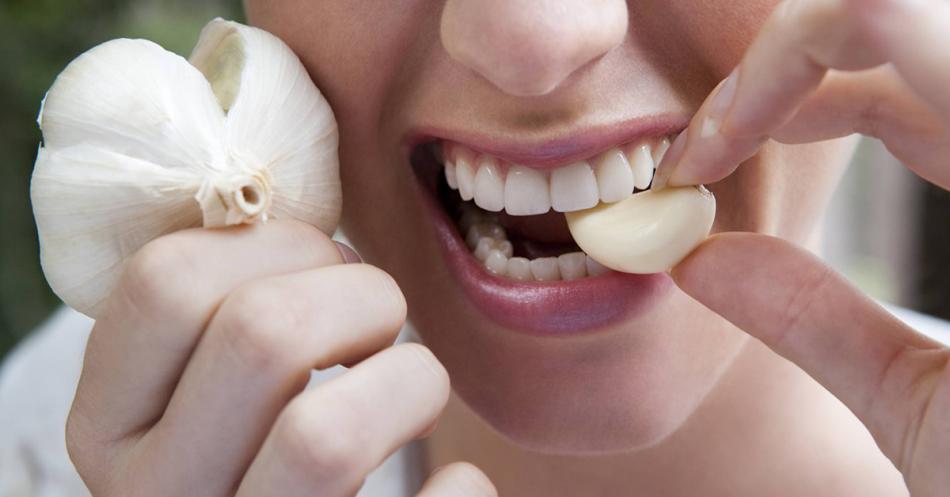 Беременная девушка откусывает кусочек от зубка чеснока