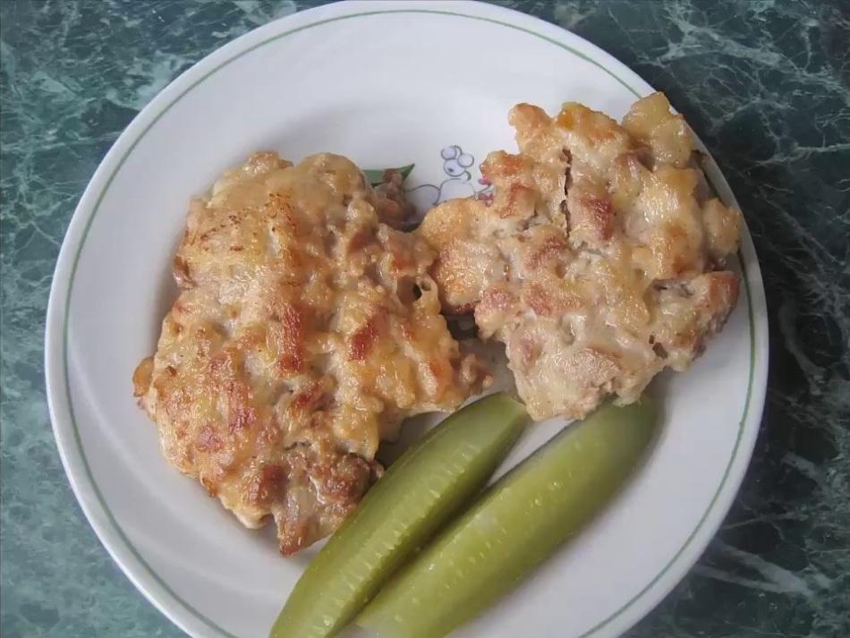 Готовые рубленные отбивные из свинины на тарелке с солеными огурцами
