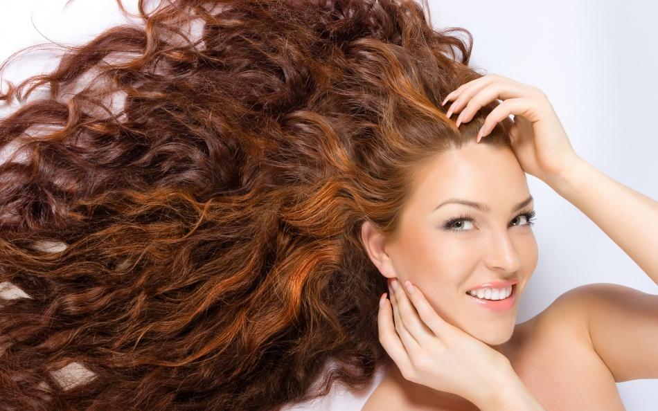 Улыбчивая девушка с длинными рыжеватыми волосами после окрашивания хной