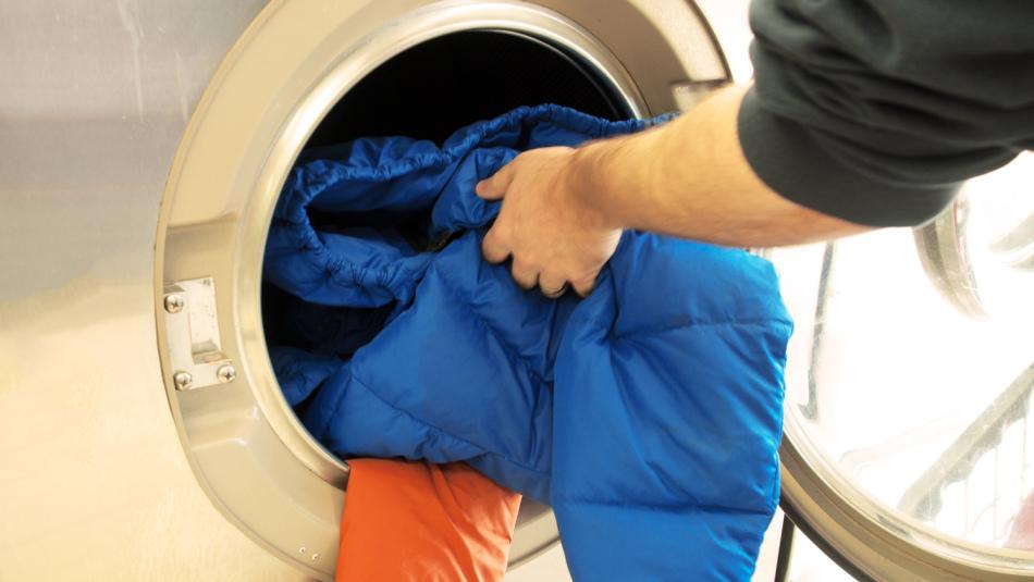 Девушка укладывает куртку в стиральную машинку посл обработки пятна от мазута на ней