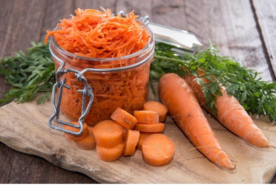 Морковь на столе в банке, целая и нарезанная кольцами