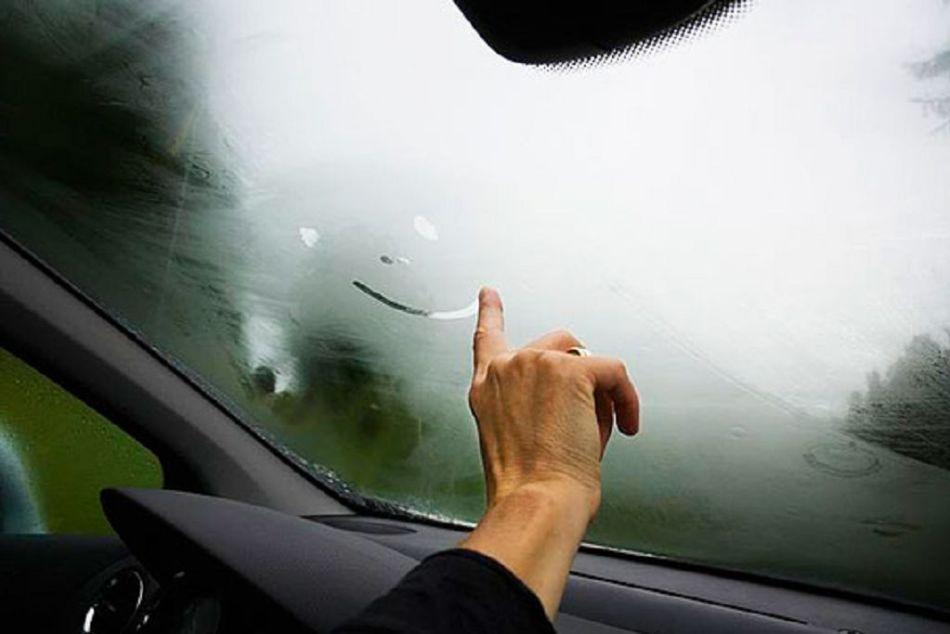 Мужская рука рисует смайлик на запотевшем окне в салоне автомобиля