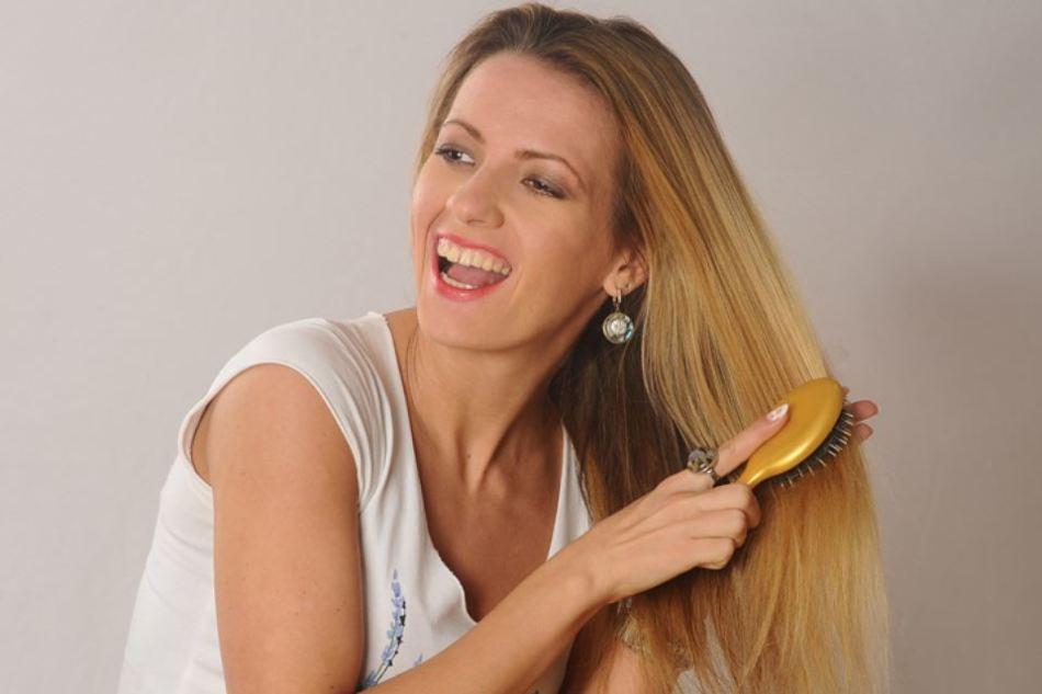 Девушка расчесывает свои волосы