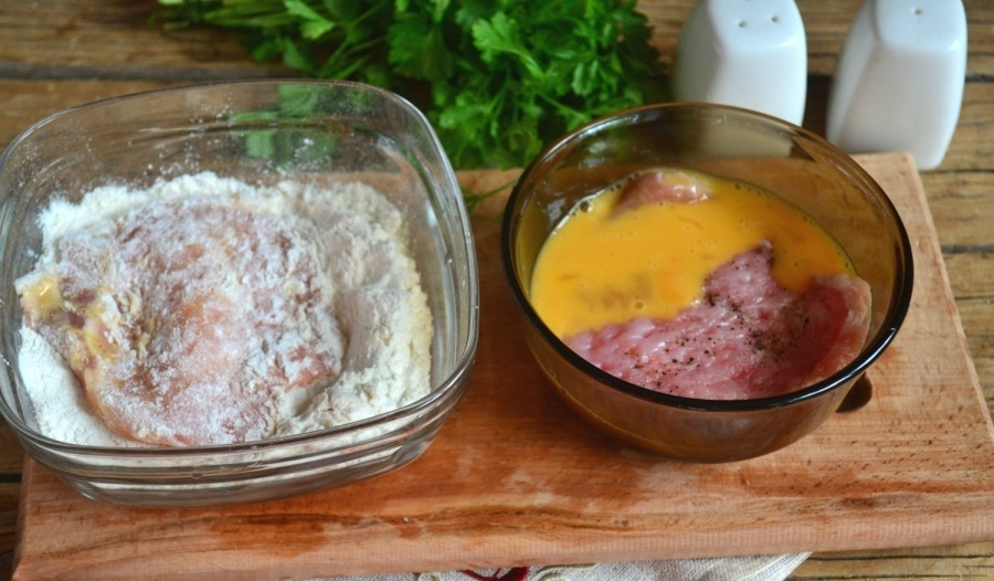 Свинные отбивные в процессе обработки яйцом и мукой перед жаркой