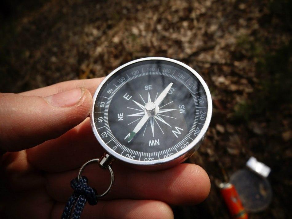 Путешественник держит в руке компас для определения направления своего движения