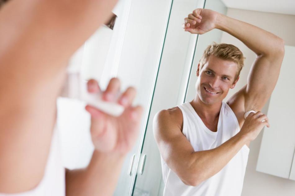Мужчина наносит антиперспирант под мышки