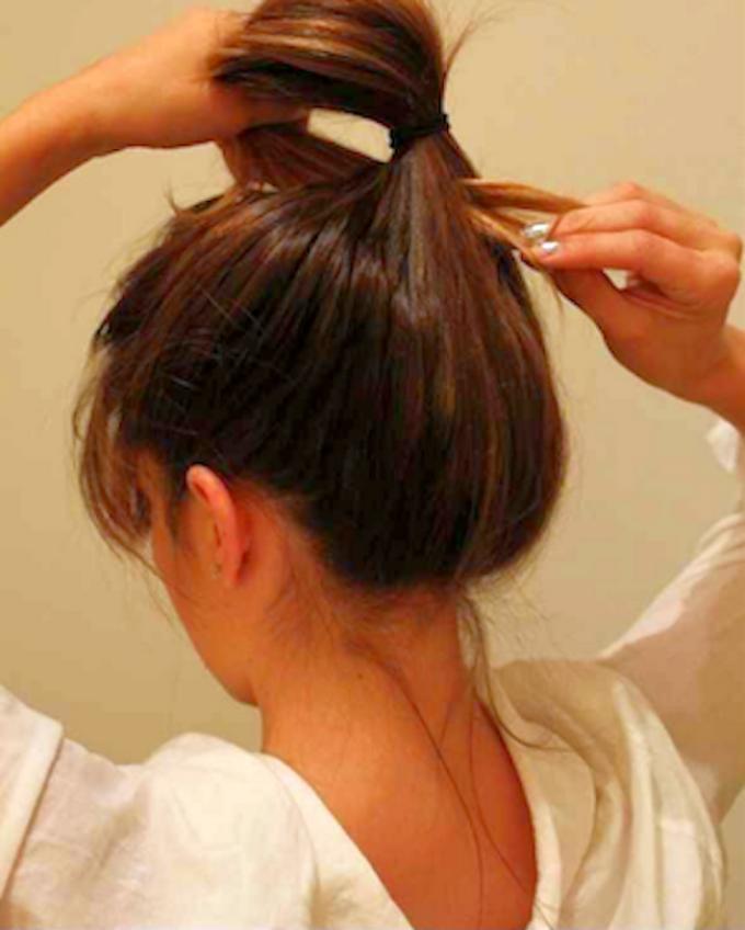 Вот так нужно продеть кончик хвоста для создания высокого пучка для длинных или средних волос