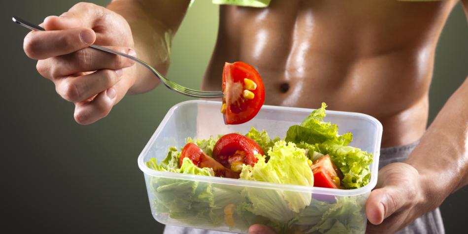 Мужчина кушает овощной салат после тренировки