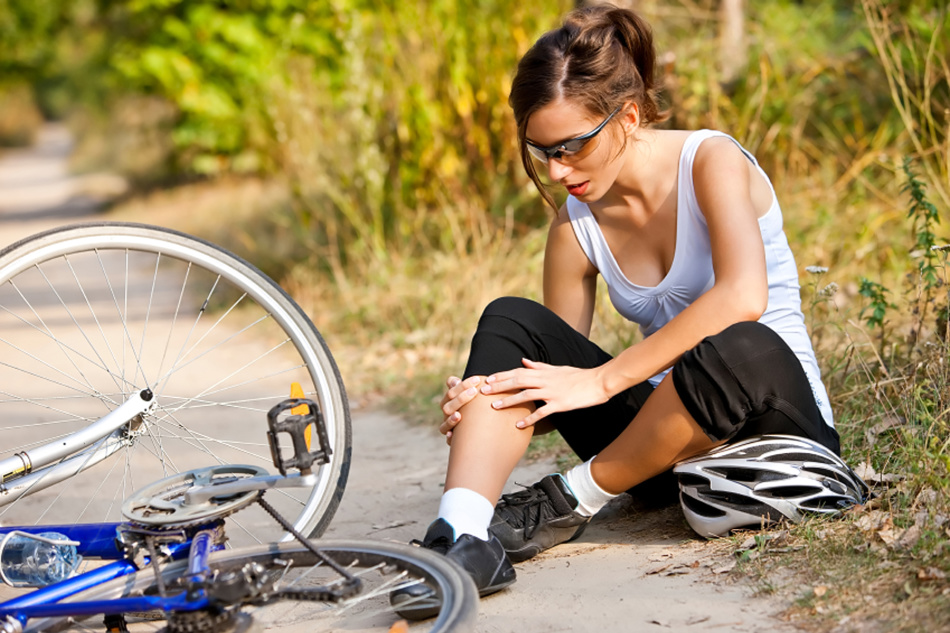 Девушка массирует колено, которое разболелось от езды на велосипеде