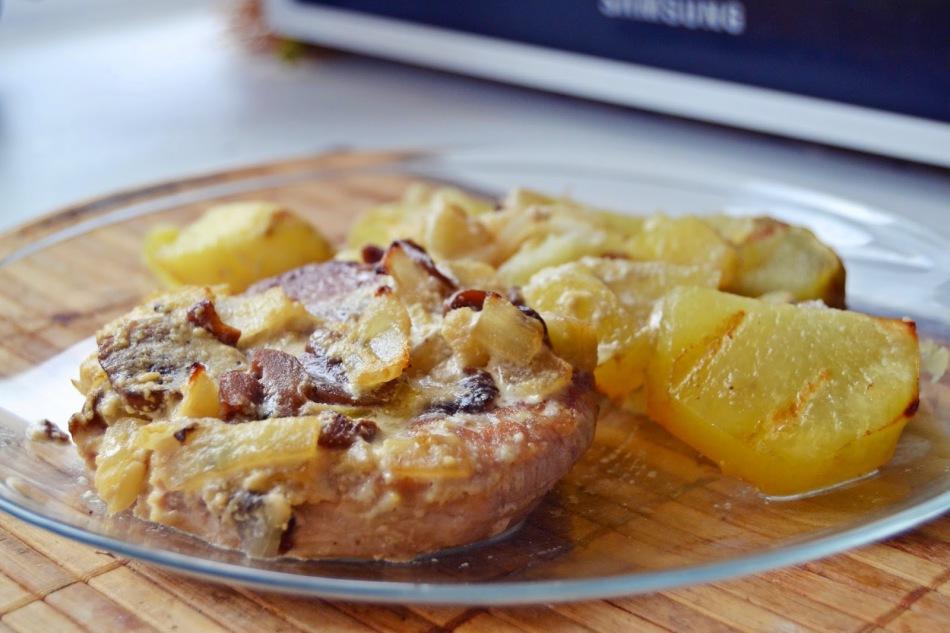 Сочная отбивная из свинины с картофелем на тарелке
