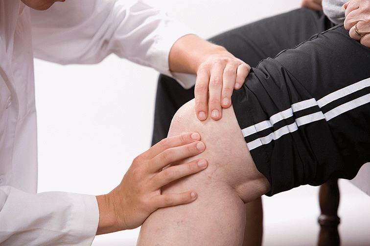 Врач обследует коленный сустав с болью сзади