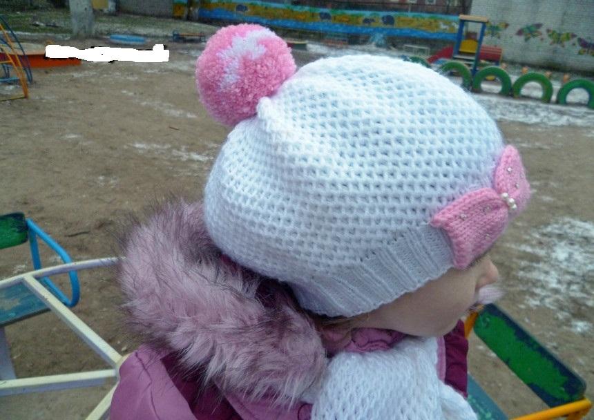 На девочке одета белая шапка, связанная узором соты