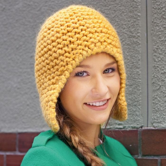 Оригинальная шапка-шлем из толстой пряжи платочным узором на девушке