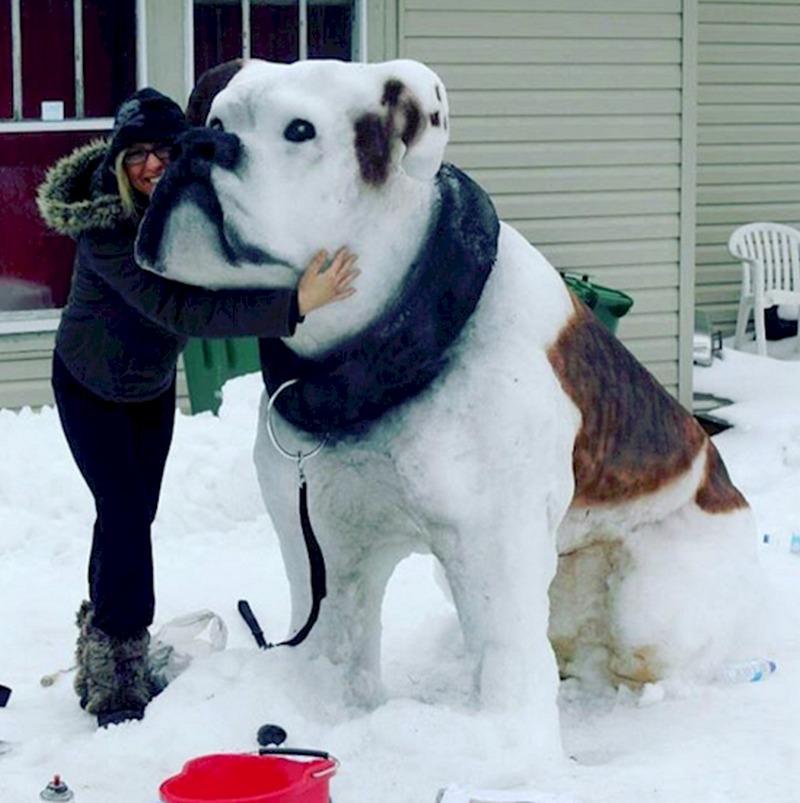 Большая снежная скульптура собаки с девушкой-автором