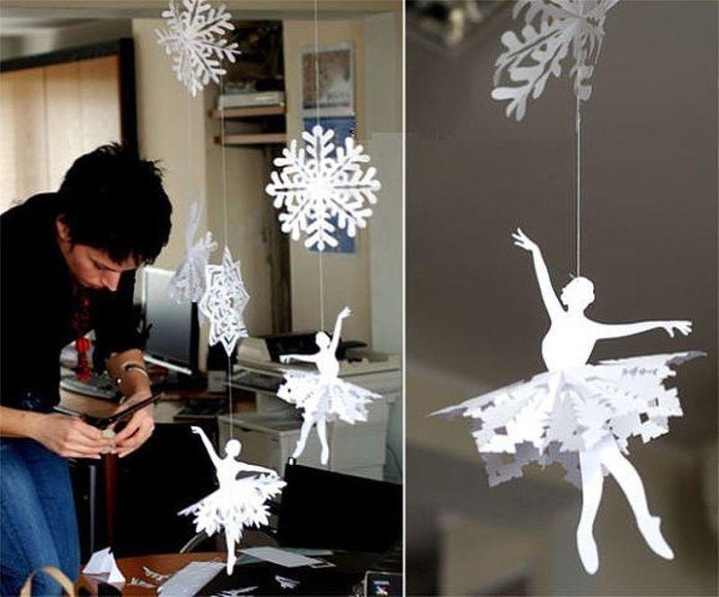 Девушка вырезает вытынанки балерин для украшения офиса